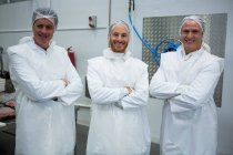 Team of butchers standing with arms crossed at meat factory — Stock Photo