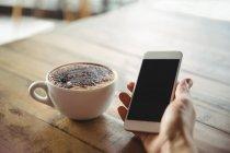 Main d'une femme tenant un téléphone portable dans un café — Photo de stock