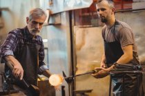 Team of glassblower forming and shaping a molten glass at glassblowing factory — Stock Photo
