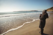 Женщина фотографирует на цифровую камеру на пляже в течение дня — стоковое фото
