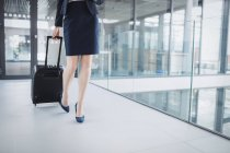 Low section of businesswoman holding suitcase walking through office corridor — Stock Photo