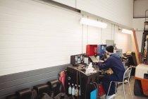 Механік, використовуючи ноутбук у ремонт гаража — стокове фото