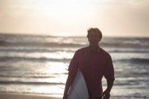 Человек с доской для серфинга стоит на пляже в сумерках — стоковое фото