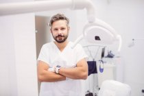 Dentist standing with arms crossed in clinic — Stock Photo