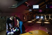 Two young people sorting bowling balls in the bowling alley — Stock Photo