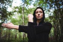 Mulher realizando exercício de alongamento na floresta — Fotografia de Stock