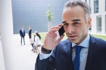 Businessman talking on mobile phone outside office building — Stock Photo