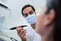 Odontoiatra che visita una paziente di sesso femminile in clinica — Foto stock