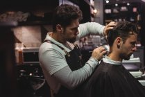 Man getting hair trimmed by hairdresser with razor in barber shop — Stock Photo