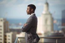 Vue latérale de l'homme d'affaires debout avec les bras croisés sur la terrasse du bureau — Photo de stock