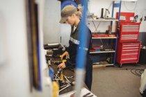 Female mechanic checking a car parts in repair garage — Stock Photo