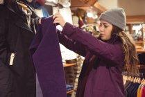 Femme sélectionnant des vêtements dans un magasin de vêtements — Photo de stock