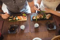Partie médiane du couple ayant des sushis au restaurant — Photo de stock
