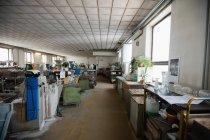 Estación de trabajo vacía y maquinaria en la fábrica de soplado de vidrio - foto de stock