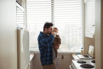 Father having coffee while holding baby in kitchen — Stock Photo