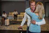 Pareja feliz abrazándose en la sala de espera en la terminal del aeropuerto - foto de stock
