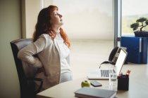 Schwangere Geschäftsfrau hält sich im Büro auf Stuhl zurück — Stockfoto
