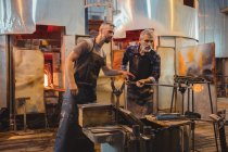 Team of glassblower shaping a molten glass at glassblowing factory — Stock Photo