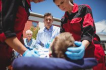 Paramedics examining injured boy on street — Stock Photo