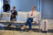 Mulher sentada na cadeira na área de espera no terminal do aeroporto — Fotografia de Stock