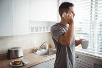 Man talking on mobile phone while having coffee in kitchen at home — Stock Photo