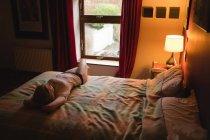 Mujer acostada en la cama en el dormitorio — Stock Photo