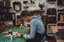 Зрілі craftswoman ковкою шкіри в майстерні — стокове фото