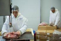 Fleischereifachverkäuferin schneidet Fleisch mit Fleischschneidemaschine in Fleischfabrik — Stockfoto