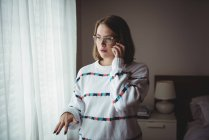 Woman standing in bedroom and talking on mobile phone at home — Stock Photo