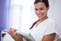 Smiling dentist using digital tablet in clinic — Stock Photo