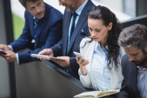 Business people using mobile phone and digital tablet in office — Stock Photo