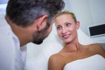 Paciente feminina sorrindo enquanto olha para o médico na clínica — Fotografia de Stock
