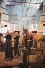 Team of glassblowers shaping a glass on the blowpipe at glassblowing factory — Stock Photo