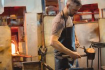 Glassblower forming and shaping a molten glass at glassblowing factory — Stock Photo