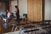 Instructor helping woman practicing pilates in fitness studio — Stock Photo
