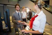Бізнесмен, даючи його інтернат передати жіночий персонал-Реєстрація реєстрації в аеропорту терміналу — стокове фото