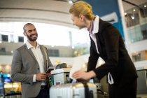 Регистрация на рейс сопровождающий прилипает к багажу пассажира в аэропорту — стоковое фото