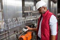 Уверенный работник мужского пола операционная машина на соковой фабрике — стоковое фото