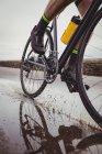 Низкая часть атлета езда на велосипеде по мокрой дороге — стоковое фото