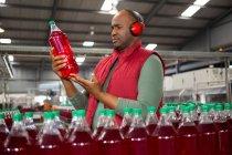 Серьезный работник мужского пола носит защитную ушную одежду во время осмотра бутылки на заводе — стоковое фото