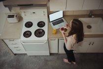 Femme regardant ordinateur portable tout en prenant le petit déjeuner dans la cuisine à la maison — Photo de stock