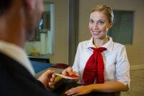 Женщины-сотрудники выдают посадочный талон бизнесмену за стойкой регистрации — стоковое фото