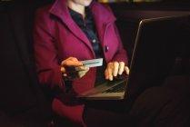 Empresaria haciendo compras en línea en la computadora portátil con tarjeta de crédito en coche - foto de stock