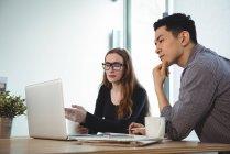 Dirigenti aziendali che discutono su laptop in ufficio — Foto stock