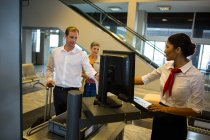 Businessman handing over boarding pass to female staff at airport terminal — Stock Photo