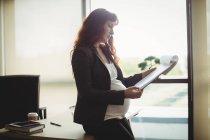 Donna d'affari incinta che legge documenti cartacei in ufficio — Foto stock