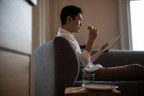 Uomo che utilizza tablet digitale mentre ha panino a casa — Foto stock
