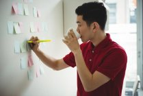 Business executive writing on sticky notes while having cup of coffee in office — Stock Photo