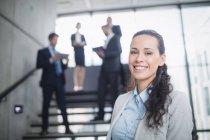 Портрет уверенной деловой женщины, улыбающейся в офисе — стоковое фото