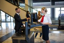 Female staff interacting with passengers at the airport terminal — Stock Photo